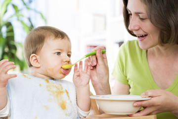 Hungry baby boy eating food next to his mother.
