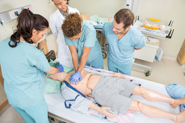 Nurses Performing CPR On Dummy Patient