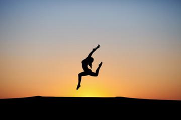 silhouette of female dancer in sunset sky