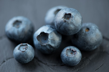 Ripe blueberries over black wooden background