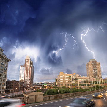 Escaping from city severe weather. Cars speeding up with lightni