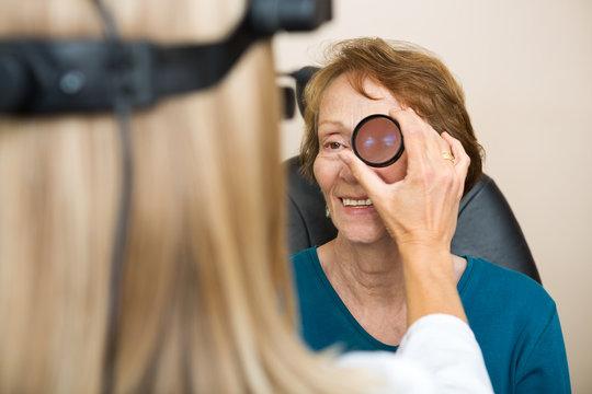 Optician Examining Senior Woman's Eye
