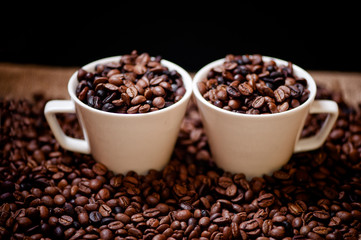 Fresh hot columbian coffee in two cups, around coffee beans