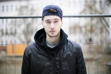 junger Mann vor einem Zaun