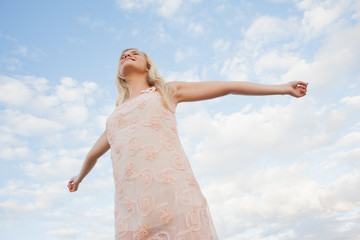 Young woman in summer dress stretching arms against sky