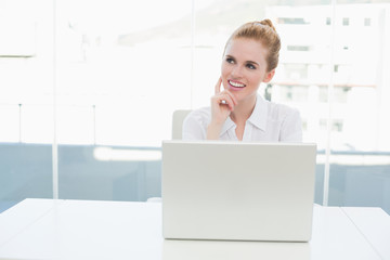 Thoughtful businesswoman with laptop at office desk