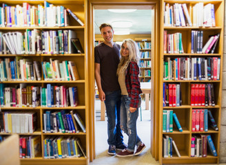 Young couple by bookshelves in the library