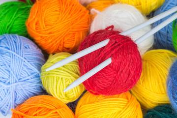 balls of wool yarn and knitting needles