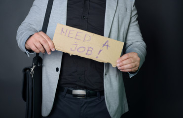 "Businessman holding sign ""need a job"""