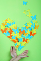 Paper butterflies on hands on green wall background