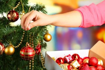 Decorating Christmas tree on bright background