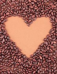Heart of sunflower grains in chocolate, on brown background