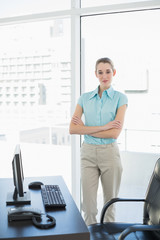 Attractive peaceful businesswoman posing with arms crossed