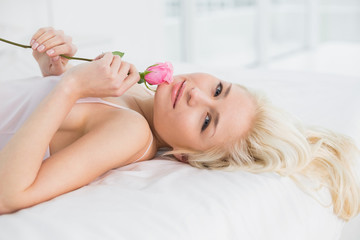 Portrait of a pretty woman resting in bed with rose