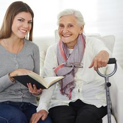 Wall Mural - Frau beim Freiwilligendienst liest Senioren vor