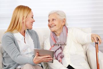 Wall Mural - Frau zeigt Seniorin einen Tablet Computer