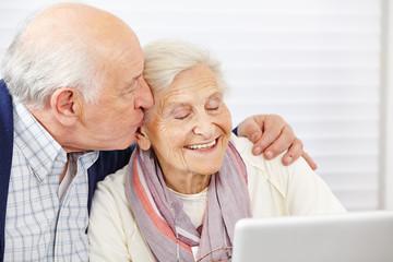 Senior küsst seine Frau am Computer auf die Wange