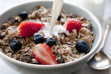 bowl of granola with fresh fruit and milk.