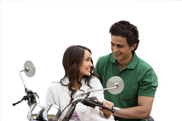 Couple looking at each other and smiling while riding a motorcycle