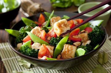 Closeup of a bowl of tofu and vegetable stir fry.