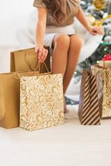Closeup on woman sitting among shopping bags near christmas tree