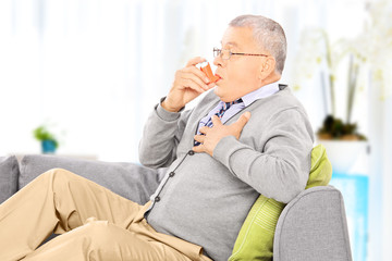 Mature man seated on a sofa taking asthma treatment at home