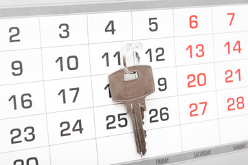 A house key on a calendar background, paying your mortgage on ti
