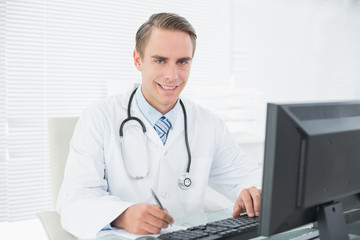 Smiling doctor writing note while using computer at medical offi