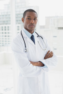 Serious doctor with arms crossed in a medical office