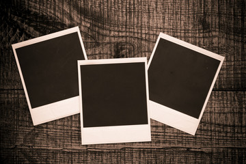 Blank photo frames on a wooden background