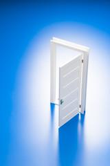 青色の背景に開いたミニチュアの扉