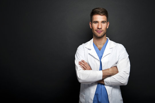 Portrait of confident young medical doctor on dark background