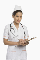 Female nurse holding a clipboard and smiling