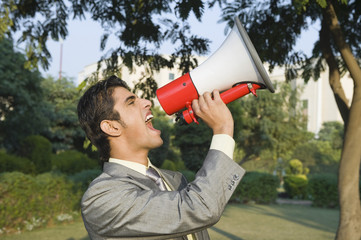 Businessman shouting into a megaphone in a park