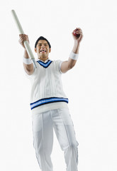 Cricket bowler cheering with a cricket ball and stump