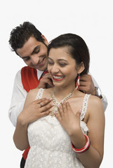 Man putting the necklace in his girlfriend's neck