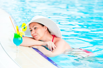 Woman in bikini and hat in the pool