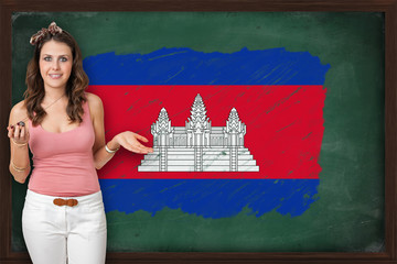 Beautiful and smiling woman showing flag of Cambodia on blackboa