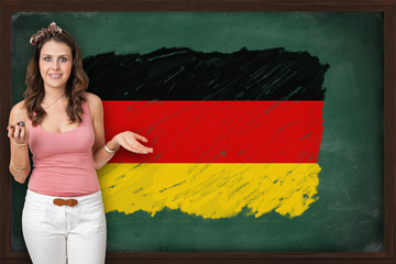Beautiful and smiling woman showing flag of Germany on blackboar