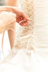 Closeup photo of hands tying ribbon on brides corset