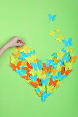 Paper butterflies on green wall background