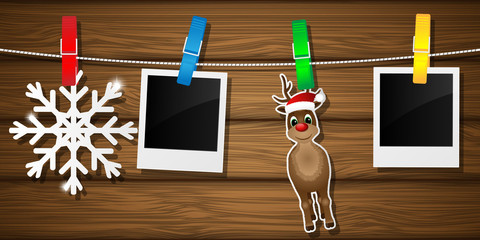 Blank photo frames, reindeer and snowflake on a clothesline