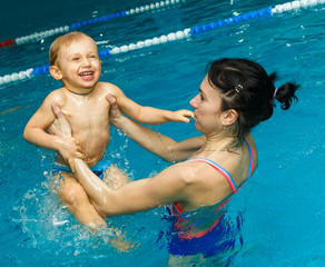 Young mother and son having fun in a swimming pool