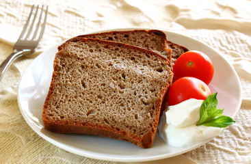 sliced bread  with spread cheese, decorated with a cherry tomato