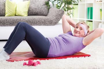 Senior woman doing curl-ups