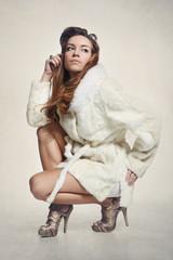 Modelka w eleganckim  białym  futrze i złotych butach