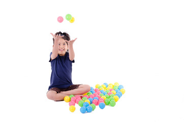 Happy little girl playing with colourful balls