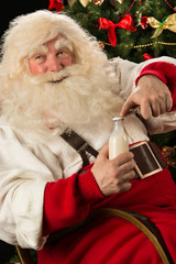 Happy Santa Claus opening glass bottle with milk against Christm