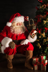 Santa putting gifts under Christmas tree in dark room