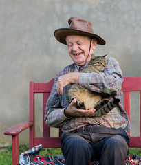 Old man hugging his cat and laughing